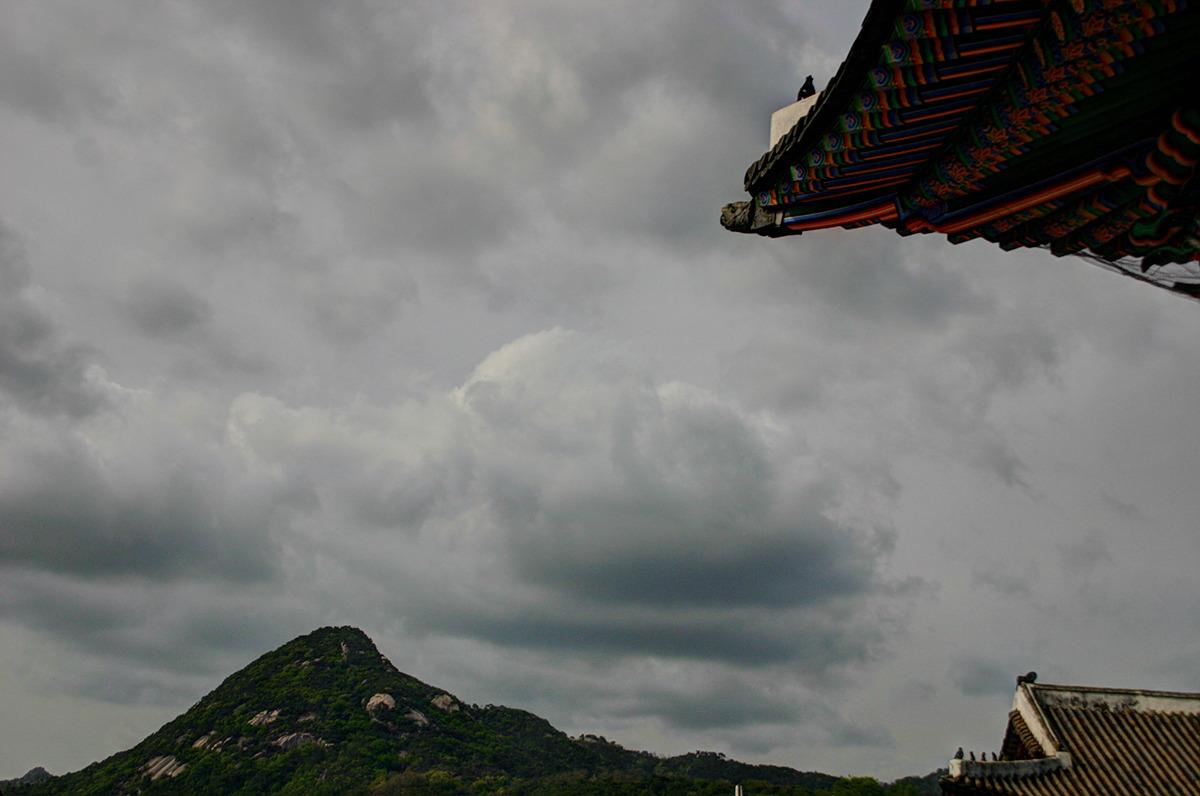 가까이는 단청처마가 보이고 조금 멀리에는 어처구니 잡상이 처마끝에 자리한 한국의 지붕이 보이며 저 너머에는 백악산이 보인다. 하늘에는 먹구름이 자욱하다.